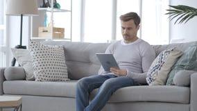 Hombre adulto que se sienta en el sofá y que usa la tableta metrajes
