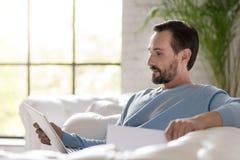 Hombre adulto serio que mira su ordenador portátil Imagenes de archivo