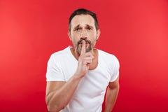 Hombre adulto serio que muestra gesto del silencio Imágenes de archivo libres de regalías