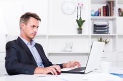 Hombre adulto serio que trabaja con el ordenador portátil en la oficina Foto de archivo