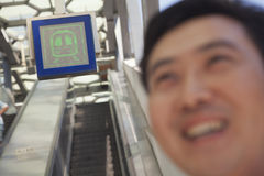 Hombre adulto sonriente en la estación de metro, tiro de la escalera móvil Imagenes de archivo