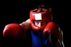 Hombre aficionado del boxeador que lucha con la protección roja de los guantes y del sombrero de boxeo Fotos de archivo