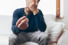 Hombre afligido que lleva a cabo un anillo de bodas imagen de archivo