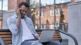 Hombre africano al aire libre que se sienta con dolor de cabeza usando el ordenador portátil almacen de video