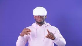 Hombre africano alegre que juega el videojuego en casco de la realidad virtual en fondo azul marino almacen de metraje de vídeo