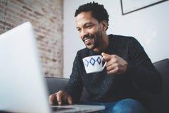Hombre africano alegre que usa el ordenador y sonriendo mientras que se sienta en el sofá Hombre negro que sostiene la taza de ce Imagenes de archivo