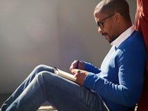 Hombre africano americano joven ocasional vestido atractivo con las gafas de sol que hacen notas en cuaderno Estudiante que se pr imagen de archivo libre de regalías