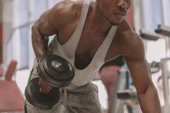 Hombre africano atl?tico que se resuelve con pesas de gimnasia en el gimnasio imagenes de archivo