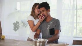 Hombre africano atractivo que prepara la pasta en la tabla de madera Su novia lo está tomando el pelo con la manzana Joven almacen de metraje de vídeo