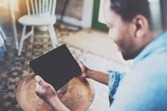 Hombre africano barbudo atractivo que usa el ordenador portátil mientras que se relaja en la butaca en oficina moderna Concepto d Imagen de archivo libre de regalías