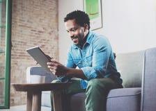 Hombre africano barbudo atractivo sonriente que trabaja en casa mientras que se sienta en el sofá Usando la tableta digital para  Fotografía de archivo libre de regalías