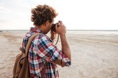 Hombre africano con la mochila que toma imágenes en la playa Foto de archivo libre de regalías