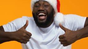 Hombre africano emocionado en el sombrero de la Navidad que muestra a pulgares para arriba, como gesto, día de fiesta almacen de video