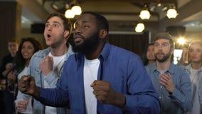 Hombre africano emocional con los amigos detrás de la victoria del júbilo, éxito del proyecto almacen de metraje de vídeo
