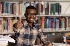 Hombre africano en una biblioteca que muestra los pulgares para arriba Imágenes de archivo libres de regalías