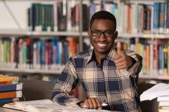 Hombre africano en una biblioteca que muestra los pulgares para arriba Fotos de archivo libres de regalías