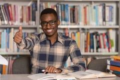 Hombre africano en una biblioteca que muestra los pulgares para arriba Imagenes de archivo
