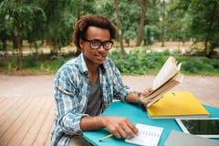 Hombre africano feliz que estudia al aire libre Imagen de archivo