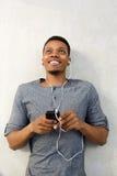 Hombre africano feliz que miente abajo escuchando la música con el teléfono móvil Imagen de archivo libre de regalías
