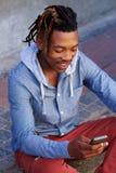 Hombre africano feliz que se sienta afuera en la acera con el teléfono móvil Foto de archivo libre de regalías