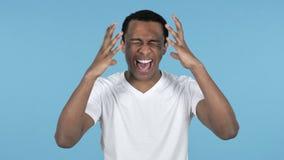 Hombre africano frustrado de griterío de los jóvenes, fondo azul almacen de video