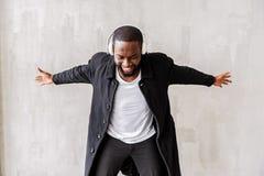 Hombre africano hermoso alegre con la barba que disfruta de sus canciones queridas vía los auriculares Imagen de archivo