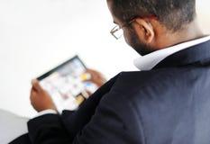 Hombre africano hermoso con el ordenador de la tablilla imagen de archivo