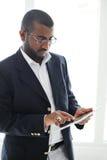 Hombre africano hermoso con el ordenador de la tablilla Foto de archivo