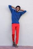 Hombre africano hermoso del cuerpo completo que sonríe con las manos detrás de la cabeza Foto de archivo libre de regalías