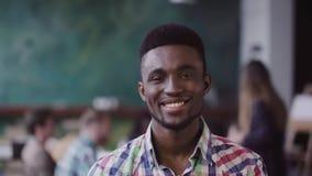 Hombre africano hermoso en la oficina moderna ocupada Retrato del varón acertado joven que mira la cámara y la sonrisa MES lento metrajes