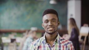 Hombre africano hermoso en la oficina moderna ocupada Retrato del varón acertado joven que mira la cámara y la sonrisa metrajes