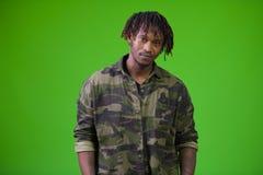 Hombre africano hermoso joven con los dreadlocks que llevan la camisa del camuflaje Fotografía de archivo