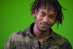 Hombre africano hermoso joven con los dreadlocks que llevan la camisa del camuflaje Imágenes de archivo libres de regalías