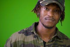 Hombre africano hermoso joven con los dreadlocks que llevan la camisa del camuflaje Imagen de archivo