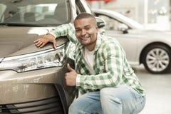 Hombre africano hermoso que elige el nuevo coche en la representación imágenes de archivo libres de regalías
