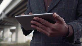 Hombre africano irreconocible que usa la tableta imágenes de archivo libres de regalías