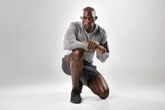 Hombre africano joven apto que se arrodilla en fondo gris fotos de archivo
