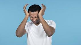 Hombre africano joven con el dolor de cabeza, fondo azul almacen de metraje de vídeo