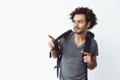 Hombre africano joven con la mochila que señala el finger lejos Fondo blanco Imagen de archivo libre de regalías