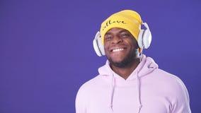 Hombre africano joven en la sudadera con capucha que sostiene los auriculares con las manos que escucha las pistas preferidas almacen de metraje de vídeo