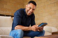 Hombre africano joven feliz con la tableta digital que se sienta en sala de estar Imagenes de archivo
