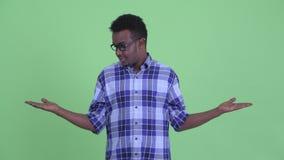 Hombre africano joven feliz del inconformista que compara algo almacen de metraje de vídeo