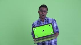 Hombre africano joven feliz del inconformista que habla mientras que muestra el ordenador portátil metrajes