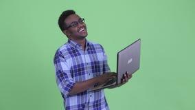 Hombre africano joven feliz del inconformista que piensa mientras que usando el ordenador portátil metrajes