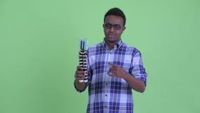 Hombre africano joven feliz del inconformista vlogging y que muestra el teléfono almacen de metraje de vídeo