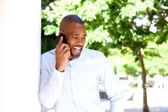 Hombre africano joven feliz que habla en el teléfono móvil al aire libre Fotos de archivo