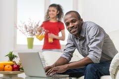 Hombre africano joven hermoso que se sienta en el sofá y que usa el ordenador portátil imagen de archivo libre de regalías