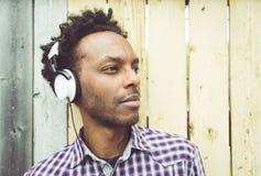 Hombre africano joven que escucha la música Imagen de archivo