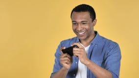 Hombre africano joven que juega al juego en Smartphone, fondo amarillo almacen de video
