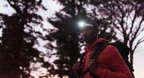 Hombre africano joven que lleva un faro que activa en la oscuridad Foto de archivo
